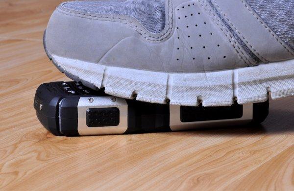 cell-phone below a sneaker