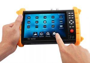 hand pointing at surveillance camera tester display