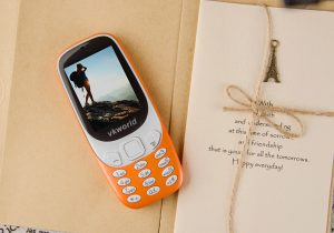 orange cell phone on a beige surface beside a gift card
